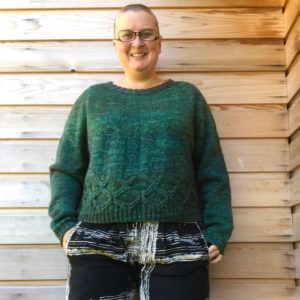 image description: lilith is standing against a wooden wall wearing a blue-green sweater with a cable detail around the hem; her hands are in her pockets & she's smiling.