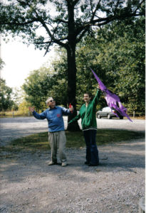 photo ID: a photo of lilith and her dad in a parking lot, being goofy & pretending to fly a kite.