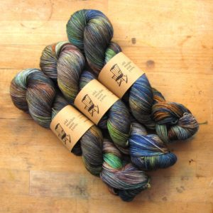 an image of three skeins of yarn in layered colours of blue, green, yellow and rust