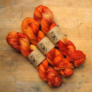photo ID: three skeins of yarn in layered shades of red, orange, and yellow.