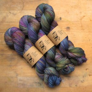 a photo of skeins of yarn dyed in purples, greens, & blues.